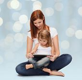 childhood, parenting and technology concept - happy mother with adorable little girl and tablet pc computer over holidays lights background
