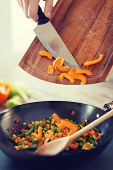 cooking, food and home concept - close up of male hand adding peppers to wok