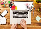 Woman working on laptop placed on wooden desk. Concept of electronic shopping. Shot from aerial view