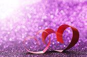 Decorative hearts of red ribbon on shiny glitter background