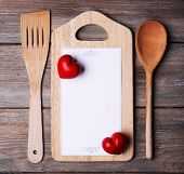 Cutting board with menu sheet of paper and hearts on rustic wooden planks background