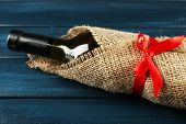 Wine bottle wrapped in burlap cloth on color wooden planks background