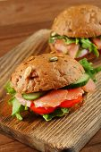 Sandwiches with salmon on cutting board, on wooden background