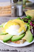 Toast with egg Benedict and avocado on plate on table close up