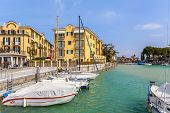 SIRMIONE, ITALY - APRIL 01, 2012: Yachts and boats at small marina and luxury hotels on background in Sirmione - famous popular tourist resort and small medieval town on Lake Garda.