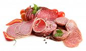 Various sliced salami with chili pepper, cherry tomatoes and spices isolated on white background