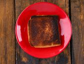 Burnt toast bread on red plate, on wooden table background