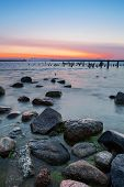 image of breaker  - Beautiful Baltic sea sunset seascape with stones in foreground old destroyed wooden pier and gate through harbor water breaker in background - JPG