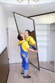 Young worker raises mirrored door on sliding wardrobe in room