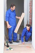 Two builders in blue overalls laid parquet in the hallway
