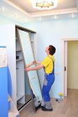 Young man setting door for sliding wardrobe in room with blue walls