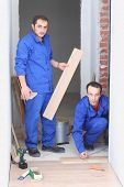 Two builder in blue overalls laid parquet in the narrow room
