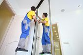 Young man in workwear fixing mirrored door on sliding wardrobe in room