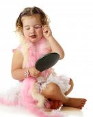 An adorable preschooler in a petticoat and pink boas applying her mommy's makeup on herself.