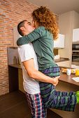 Loving couple in a passionate kiss while having breakfast