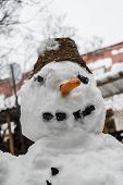 pic of snow shovel  - Smiling snowman standing with shovel in the snow - JPG