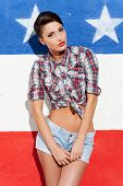 foto of young woman posing the camera  - Fashionable young short hair woman posing against American flag background and looking at camera - JPG