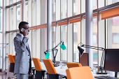 Happy smiling successful African American businessman  in a suit in a modern bright office indoors on phone