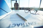 Business contract, pen, eyeglasses and touchpad on workplace and businessman on background
