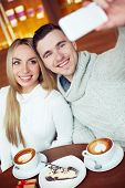 Cheerful guy and girl taking their selfie while resting in cafe