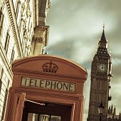 a view of a classic red telephone booth and the Big Ben in the background, in London, United Kingdom, with a filter effect