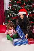 Mother And Toddler Son Open Christmas Gift