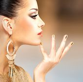Profile portrait of the beautiful fashion woman with black makeup and golden manicure