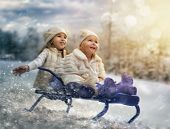 two happy girls on sled
