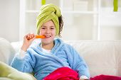 Teenager with towel on her head eating carrot, indoor