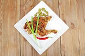 meat food : chicken legs garnished with green peas and hot chili peppers on white plates over wooden table