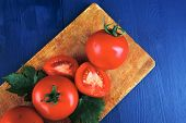 raw vegetables : some uncooked ripe fresh tomatoes on cutting board  ready to cooking over blue table