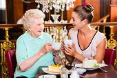 stock photo of granddaughter  - Senior woman and granddaughter drinking coffee and eating cake in cafe - JPG