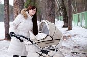 young mother with baby in stroller walks in park winter