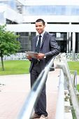 Happy business man using tablet PC outside