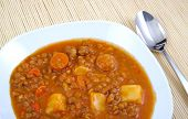 Brown cooked lentils with sausage, carrot and potato with metal spoon