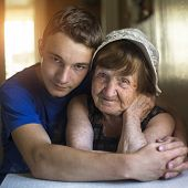 Grandmother and grandson portrait together in an embrace.