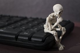 picture of thinkers pose  - Skeleton sitting on a keyboard posing as a thinker - JPG