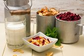 picture of cereal bowl  - Horizontal photo of scene consists of white square bowl with cornflakes two cups with dried berries and apples glass of milk green herbs and aluminum can - JPG