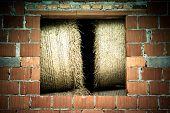 stock photo of hay bale  - Bales of hay in the window of brick barn - JPG