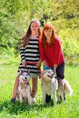 picture of dog park  - mother and daughter along with two dogs in park on background of green trees - JPG