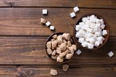 stock photo of sugar cube  - White and brown sugar cubes in bowls on dark painted wooden planks - JPG