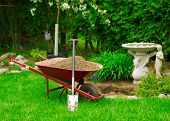 foto of wheelbarrow  - A red Wheelbarrow sits full of dirt in a lush green garden as spring gardening work is underway - JPG