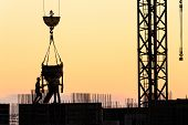 image of concrete pouring  - Builders poured concrete in a new building at sunset - JPG