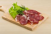foto of salami  - Sliced Salami with rosemary on the wooden bckground - JPG