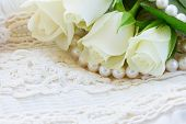 stock photo of mother-of-pearl  - white fresh  roses with lace and pearls jewelery - JPG