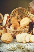 stock photo of fresh slice bread  - Assortment of sliced fresh bread on a table and in a basket - JPG