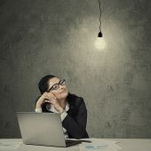 picture of lightbulb  - Female asian manager working on desk with laptop and paperwork looking at bright lightbulb - JPG