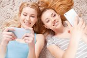 stock photo of pajamas  - Selfie time. Two young beautiful blond girls wearing pajamas lying on the light floor, smiling and making selfie top view