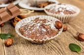 stock photo of chocolate muffin  - Cocoa and chocolate muffin with hazelnut and sugar on wood table - JPG