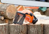 stock photo of chainsaw  - Close up of orange helmet with headset and protective mask on wooden logs chainsaw working in background - JPG